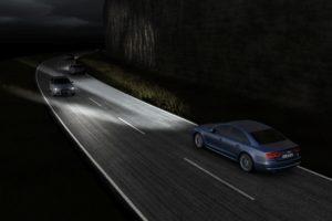 автомобиль освещает дорогу